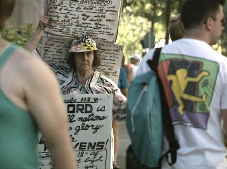 A woman wearing several poster boards with hand-written biblical passages and homophobic rants on them moves through a crowd of Gay Games registrants.