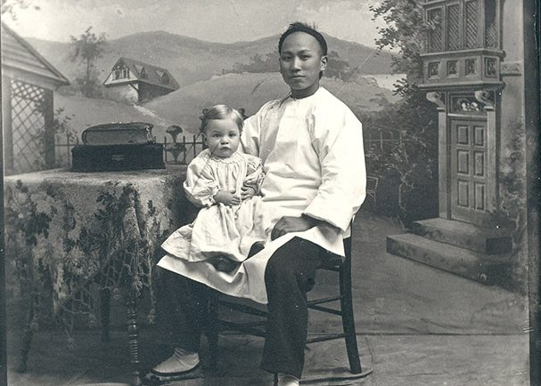 Chinese domestic worker sitting in a chair posing for a photograph with a young child on his right knee.