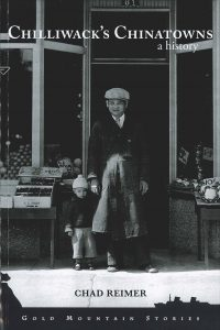 "Front cover of the book, ""Chilliwack's Chinatowns: A History,"" by Dr. Chad Reimer. The cover has a black and white photo of a young boy and a man standing hand in hand in front of a merchant's store. Fruit stalls are to the left and vegetable stalls are to the right."