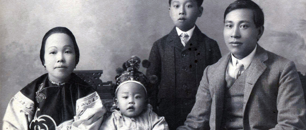 Formal black and white portrait of who is assumed to be the Yip On family. The youngest is in the centre wearing a crown with the mother on left and father on right. Their young boy is standing off centre behind the seated family.