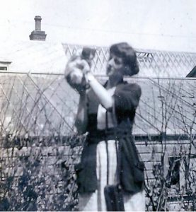 Black and white picture. Of women holding a cat she is standing in front of two glass roofed buildings.