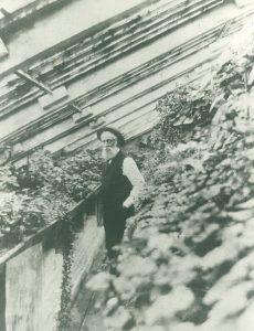 Image noir et blanc d'un homme debout dans une pièce avec beaucoup de plantes différentes. Un plafond fenêtré incliné - l'homme, vêtu de pantalon noir, une veste sombre, chemise blanche avec une longue barbe grise. Il a une longue barbe blanche et porte un chapeau circulaire.