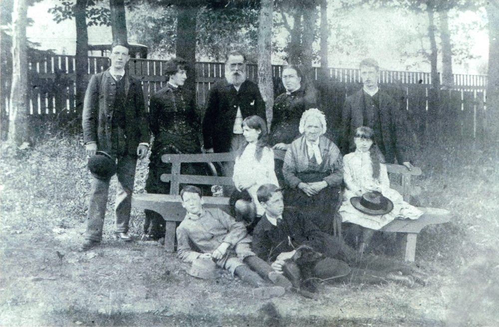 Black and white photo of a family in a courtyard surrounded by trees and a wooden fence. In this picture, there are ten people. Five people are standing, three are sitting on a bench, and two are lying on the ground in the grass. They dress all their best Sunday.