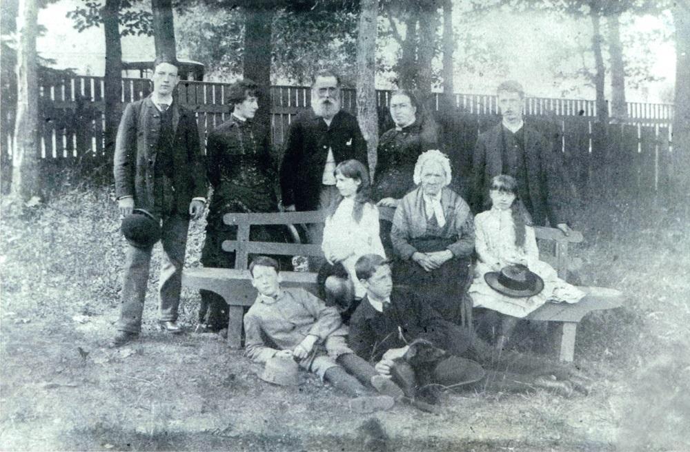 Photo noir et blanc d'une famille dans une cour entourée d'arbres et d'une clôture en bois. Dans cette image, il y a dix personnes. Cinq personnes sont debout, trois sont assis sur un banc, et deux sont couchés sur le sol dans l'herbe. Ils s'habillent tous leurs meilleurs dimanche.