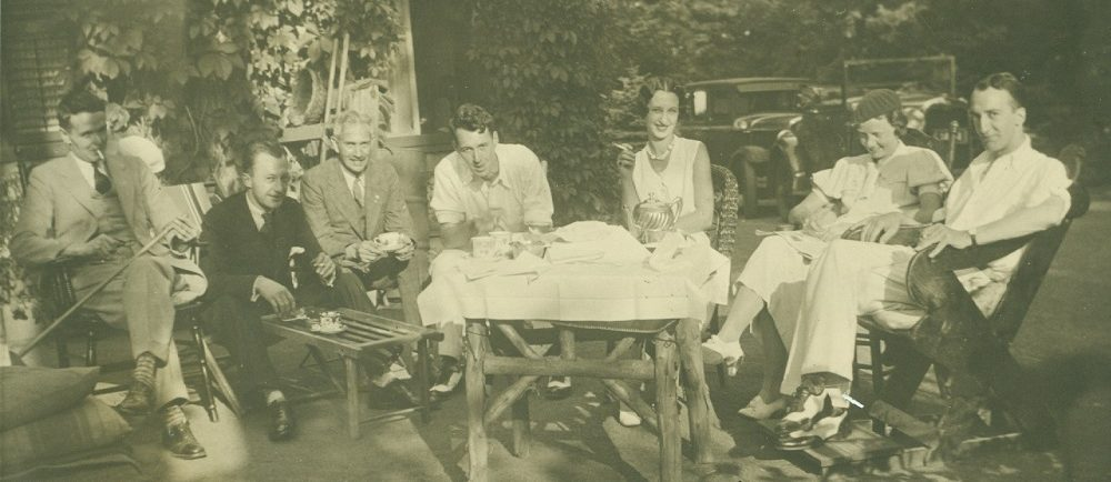 image sépia de gens assis sur des chaises autour d'un ensemble de thé sur une table recouverte de lin blanc