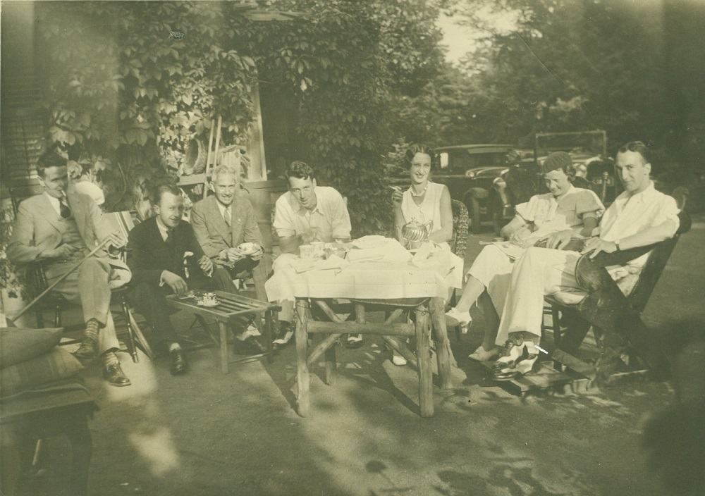 Sepia picture of people sitting in chairs around a tea set on a table covered in white linen