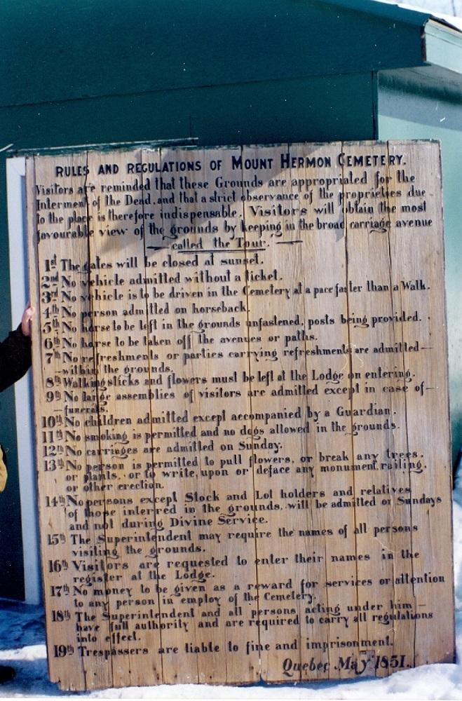 Image colorée d'une enseigne en bois avec lettrage noir. Un cadre vert foncé entoure la planche de bois