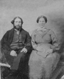 Une photo en noir et blanc d'un couple est assis, vêtue de vêtements d'époque. La femme est à droite de l'homme tout en tenant un livre.