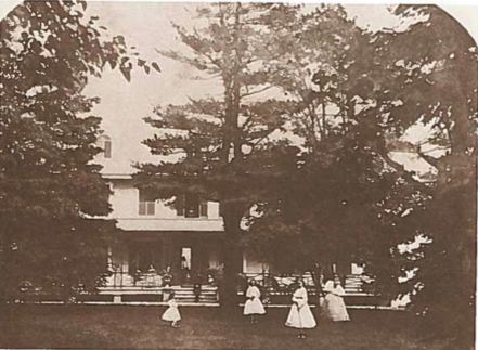 Yellow and orange photo of a house shrouded by conifer trees. There are women dressed in white dresses in front of the house on the grass by a big tree.