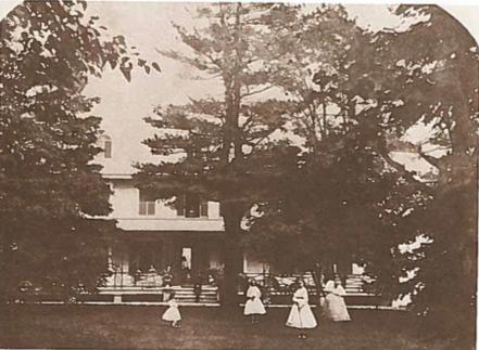 Photo jaune et orange d'une maison par enveloppées arbres conifères. Il y a des femmes vêtues de robes blanches devant la maison sur l'herbe par un grand arbre.
