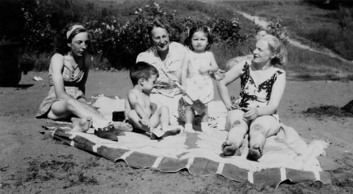 Black and white picture of a group of people sitting on the beach. There are three women dressed in beach attire and a little boy and girl. They are all on a large white sheet.