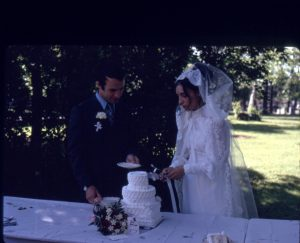 Coloured picture of a man and a woman cutting a wedding cake at their wedding