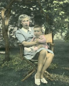 coloured picture of a woman holding a baby boy in her lap. they are outside my a large tree.
