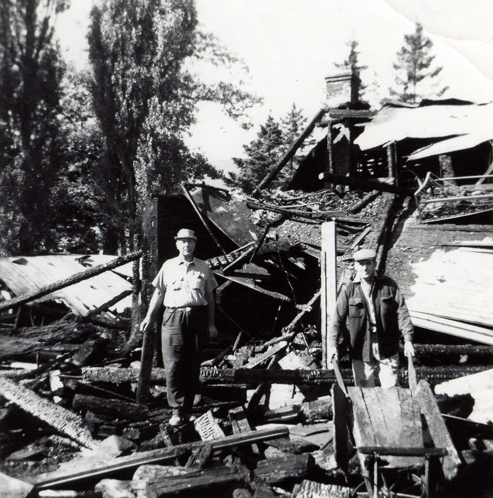 Black and white picture of a man standing in the middle of rubble after a fire