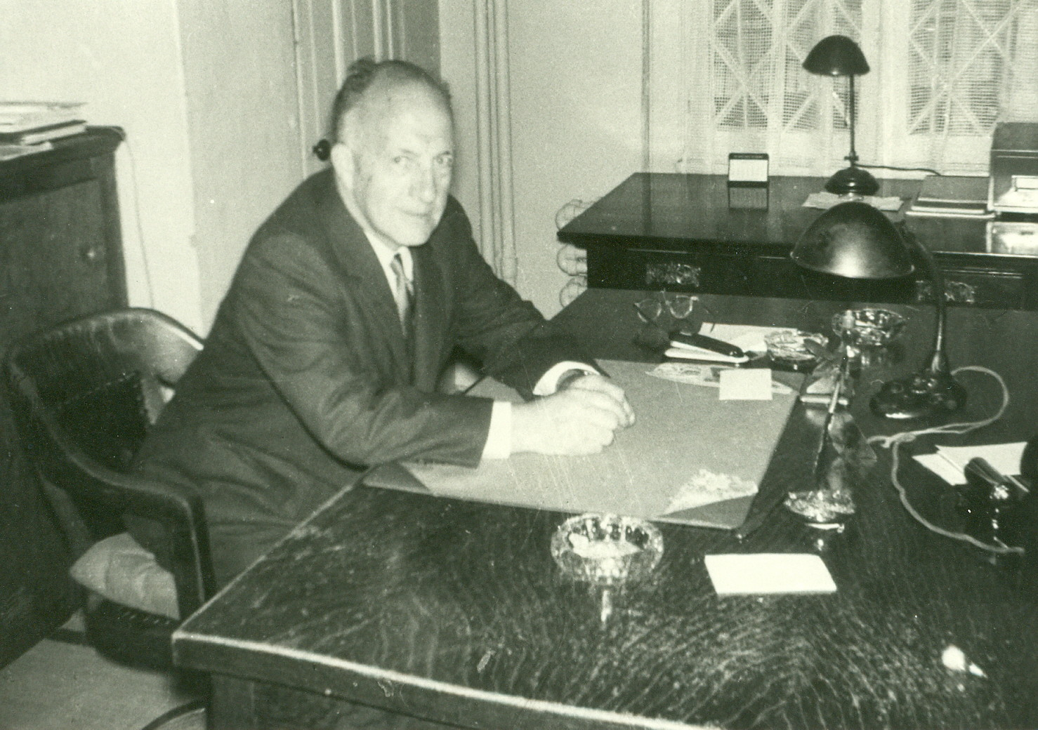 Green and white picture of an old man sitting at a large wooden desk.