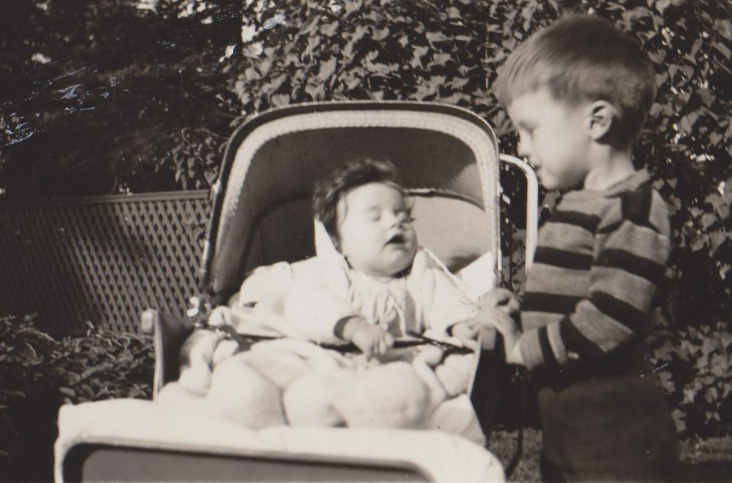 Black and white picture of a little boy and a little baby in a carriage