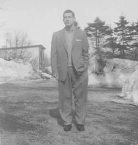 Gray photo of a man standing in front of building