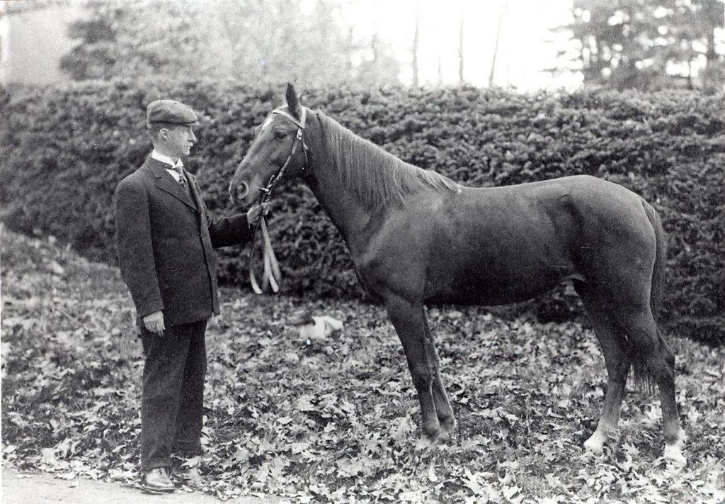 photo en noir et blanc d'un homme vêtu d'un costume tenant les rênes d'un petit cheval. Ils sont debout devant une haie de cèdres sur un chemin de gravier.
