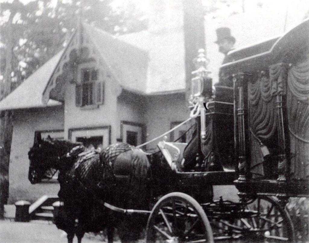 Black and white picture of a funeral procession, with a horse-driven hearse and a man wearing a top hat