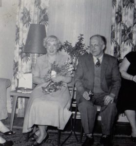 Black and white picture of an older couple at a party dressed in their best sitting by a large window