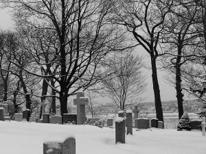 Black and white picture of a cemetery in the winter with bare trees and snow on the ground