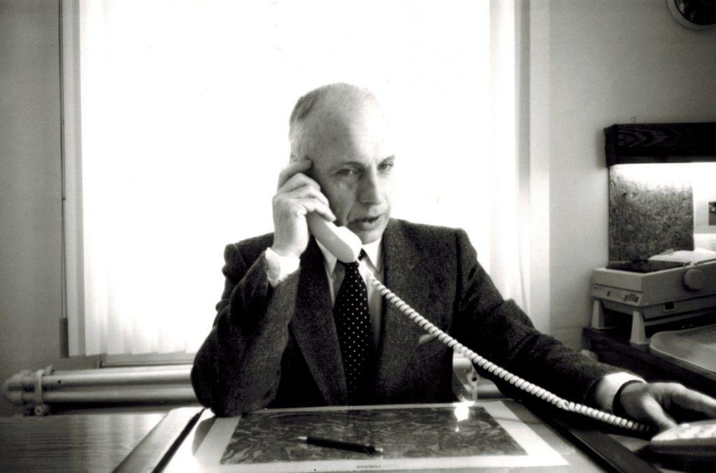 photo en noir et blanc d'un homme vêtu d'un costume tenant un téléphone à son oreille dans un bureau