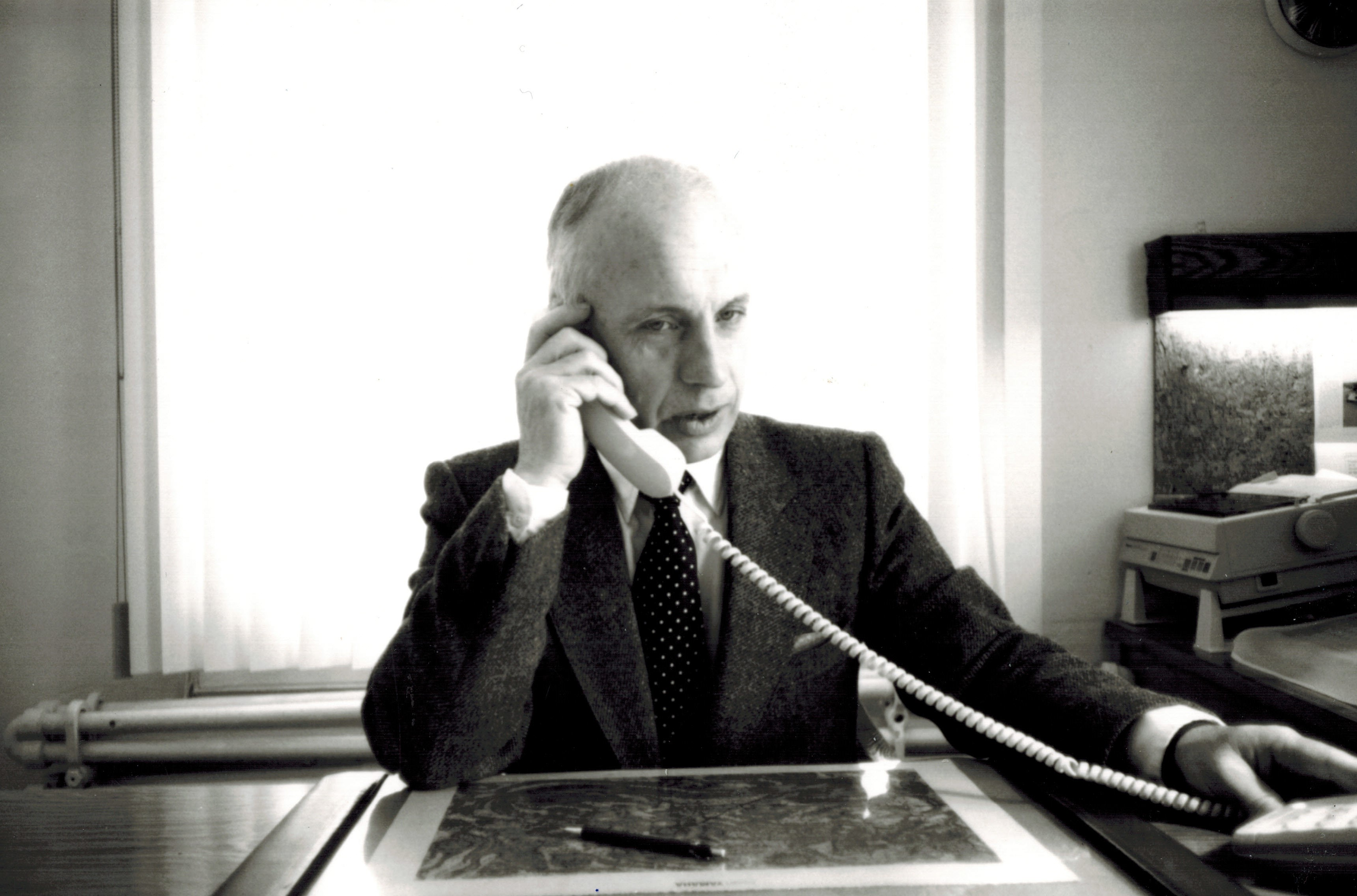 Black and white picture of a man dressed in a suit holding a phone to his ear in a office