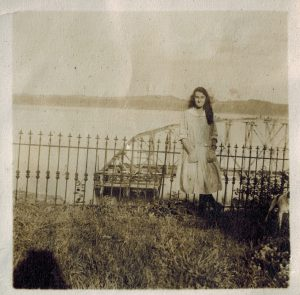 sepia photo of a girl dressed in a white dress in front of a bridge