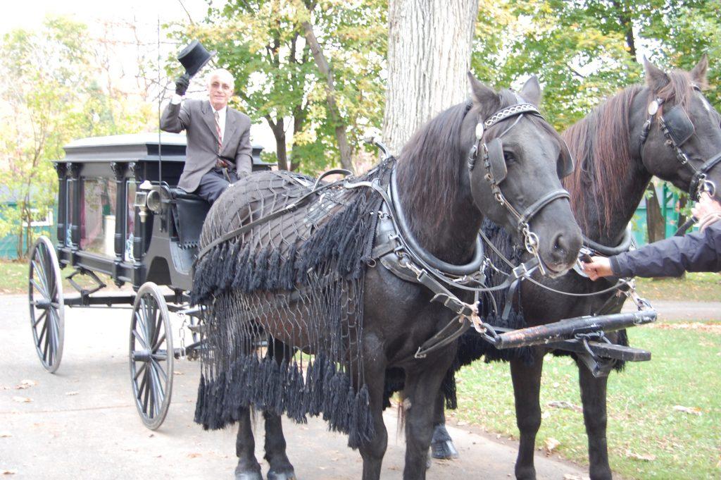 photo couleur d'un homme assis devant un corbillard tiré par des chevaux avec deux grands chevaux.