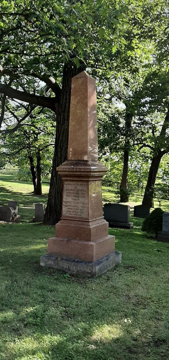 Image colorée d'une pierre tombale rougeâtre dans l'herbe et entourée d'arbres