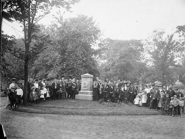 Black and white picture of a large group of people surrounding a cemetery monument for a picture