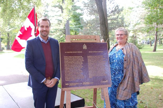 Man and woman standing on either side of a commemorative plaque for the National Historic site of Canada with a Canadian flag in the background