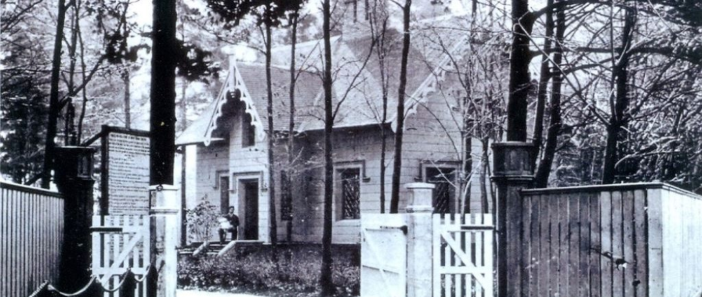 Black and white picture of a house in the woods. A man is sitting on the front step holding a white-clothed baby. There is also a large wood fence in front of the house.