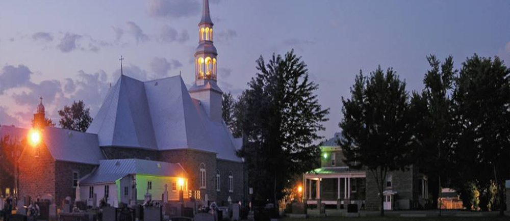 Color photograph, long shot taken at night, back view of church, presbytery and cemetery, the exterior lights of the church are lit.