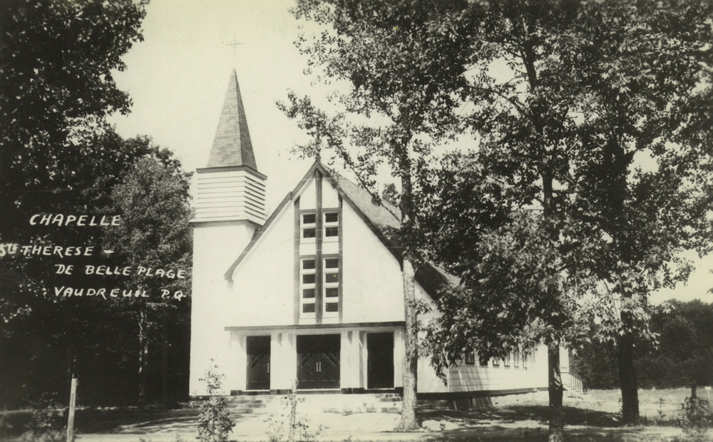 Old black and white photograph taken in summer, close-up of a white wood church facade, the steeple is placed at the top of a tower on the church's left side.