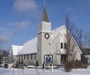 Color photograph taken in winter, close-up of a white wood church facade, the steeple is placed at the top of a tower on the church's left side, in front, a sign reads: City Hall.