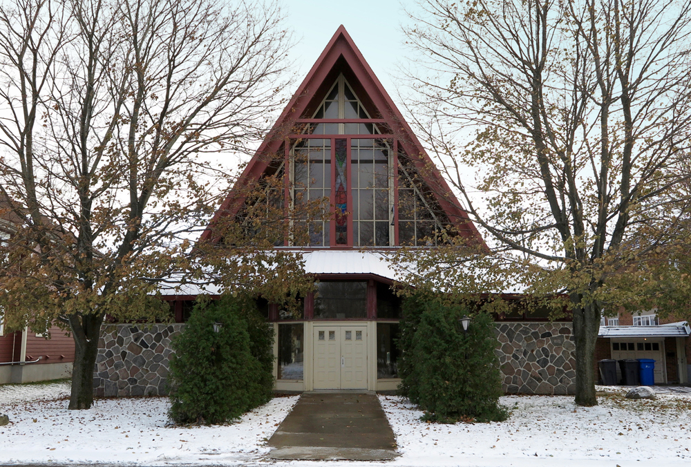 Color photograph taken in winter, close-up of church facade on which the lower part of the walls is covered in stones, the gabled roof contains stained glass windows and there are trees on either side.