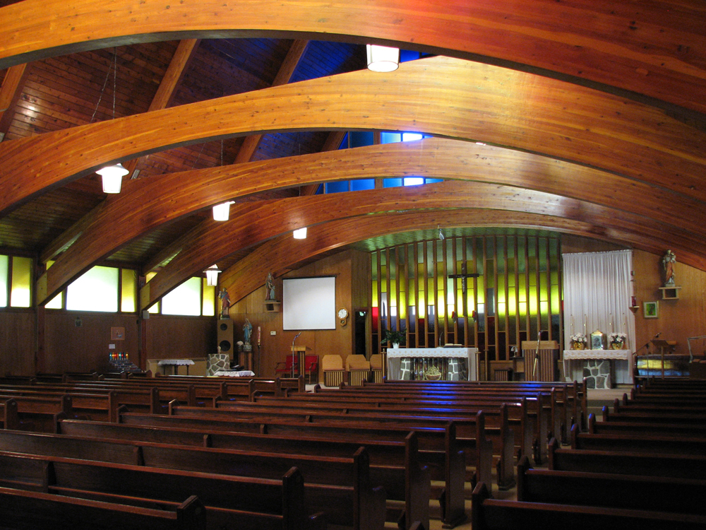 Color photograph, church interior with exposed curved wood beams and framework