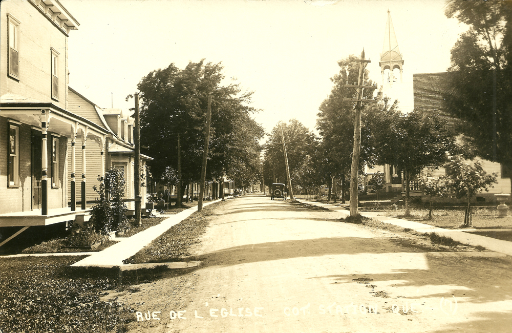 Black and white photograph, long shot of a village street, on each side are houses and a sidewalk, in the background a church steeple is visible above the trees.