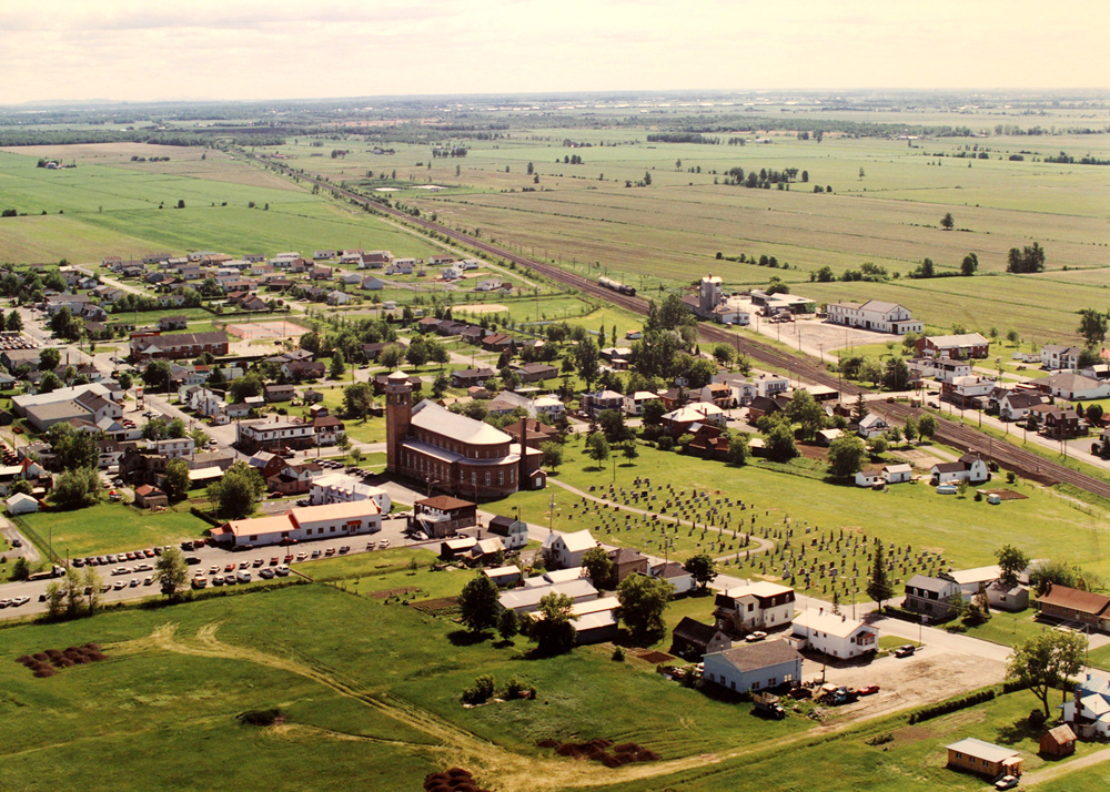 Color photograph, aerial view of a village with a church in the center, the village is surrounded by farm land.
