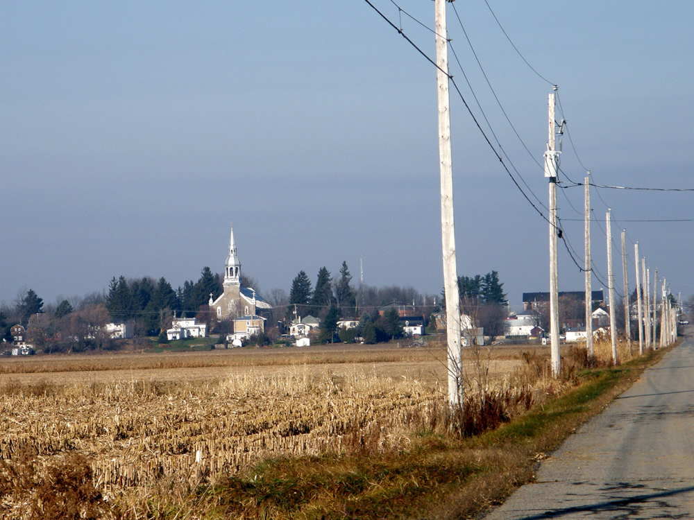 Color photograph, long shot of a church in the center of a village, in the foreground, a field and electric poles bordering a paved road.