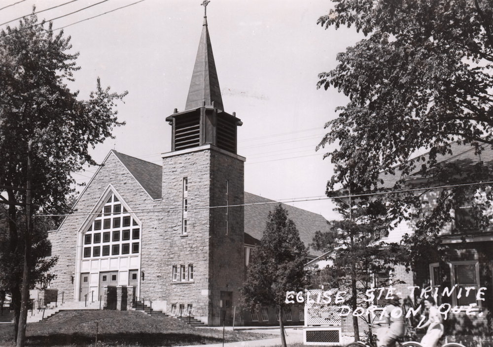 Old black and white photograph of a stone church facade and presbytery, in the foreground on the right, two young girls are riding bicycles.