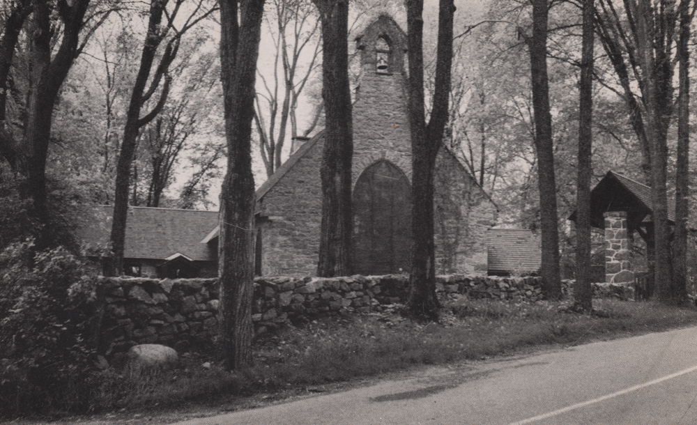 Old black and white photograph, stone church facade surrounded by trees, in the foreground, a low stone wall borders a paved road.