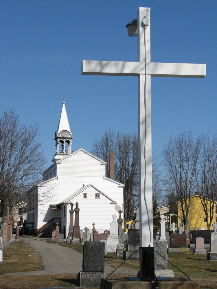 Color photograph, back view of a church, in the foreground, a cemetery and a big white cross.