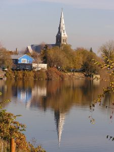 Color photograph, long shot of a church steeple, a house and trees on the waterfront and their reflection on the water.