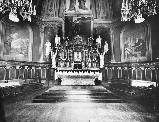 Old black and white photograph, long shot of richly decorated church interior and liturgical furnishings, statues and religious paintings.