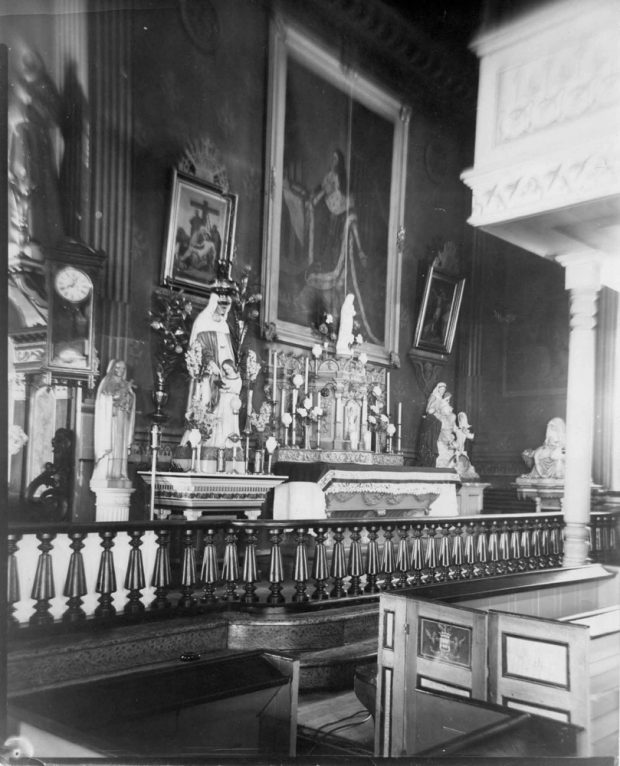 Old black and white photograph, close-up of church interior, richly decorated chapel with liturgical furnishings, statues and paintings, in the foreground, a varnished wood railing and pews.