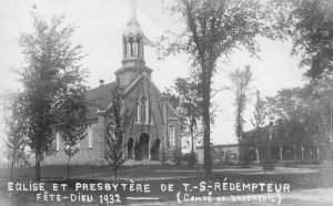 Old black and white photograph, facade of a stone church and presbytery surrounded by trees, the church is decorated with ribbons attached to the steeple and flowing down to the church steps.