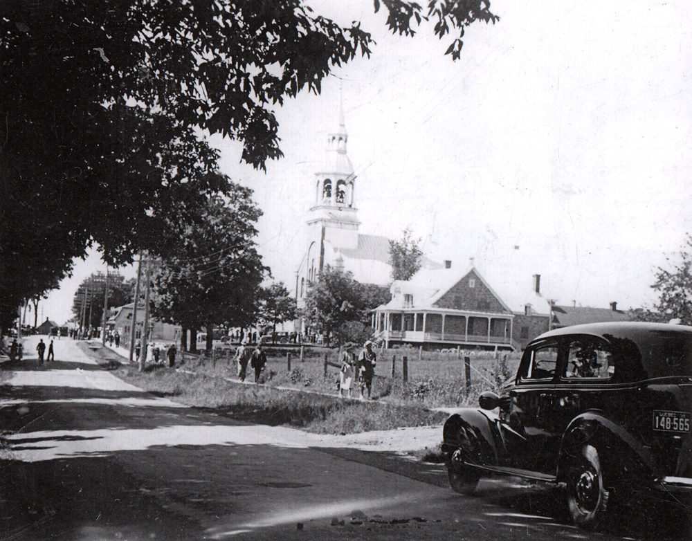 Old black and white photograph, in the foreground, a road, car and people walking on the sidewalk, in the background, a church steeple and presbytery.