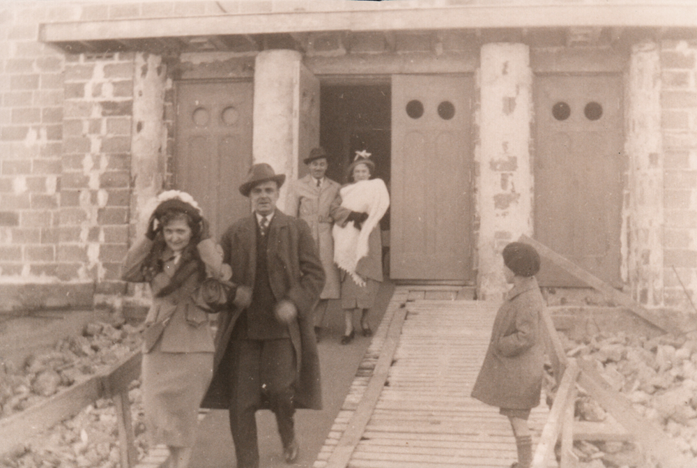 Old black and white photograph, a child and two couples, including a woman holding a baby, are exiting through the front doors of a church under construction.